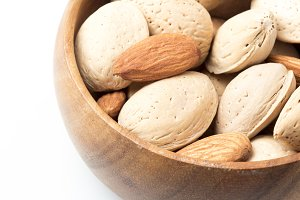 Almonds with Shells in wooden bowl