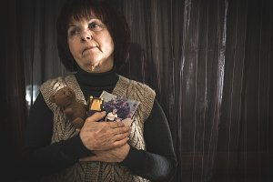 Senior woman hold pictures of childr