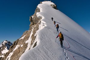 Tied climbers summiting a mountain