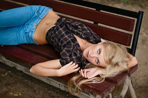 sexy blonde lies on a bench