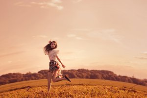cheerful girl running on the field